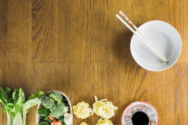 Ciotola e bacchette vicino ingredienti alimentari cinesi