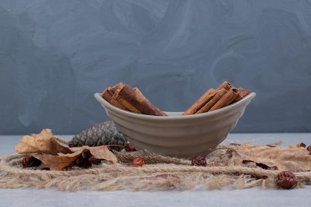 Ciotola di bastoncini di cannella, foglie e corda su tela. foto di alta qualità