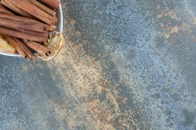 Ciotola di bastoncini di cannella su sfondo marmo.