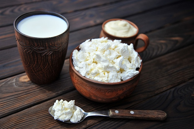 A bowl of clay with cottage cheese a mug of clay with sour cream a mug with milk and a spoon on a wooden table