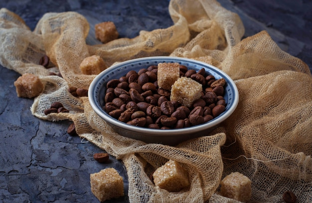 Bowl of coffee beans and brown cane sugar. selective focus