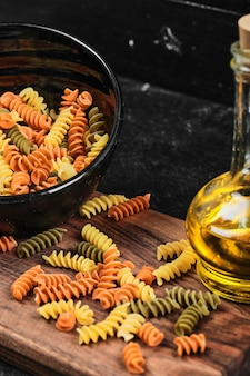 Bowl of colorful fusilli pasta and bottle of oil on dark table.
