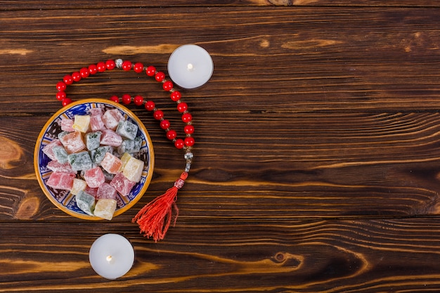 Bowl of colorful lukum and red holy rosary beads with lighted candles on wooden surface