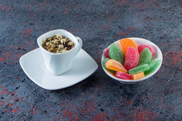 Bowl of colorful marmalades with cup of hot tea on dark surface.