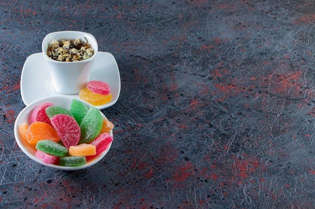 Ciotola di marmellate colorate con tazza di tè caldo su superficie scura.