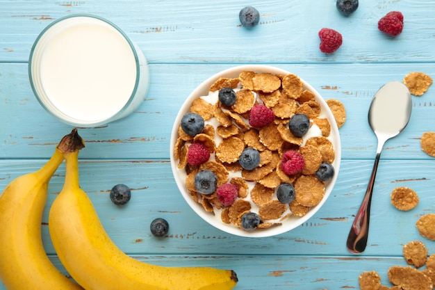 Bowl of corn flakes and fresh berries and fresh fruits on blue background.