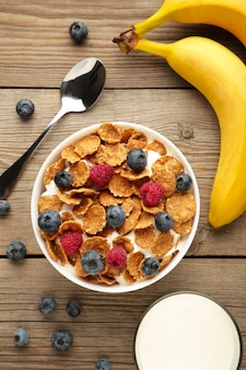 Bowl of corn flakes and fresh berries and fresh fruits on grey background.
