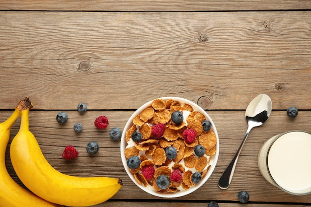 Bowl of corn flakes and fresh berries and fresh fruits on grey wooden background. top view.