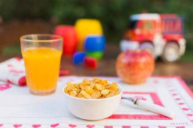 Bowl of corn flakes, juice and apple on table