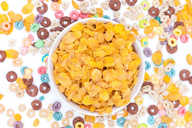 Bowl of corn flex cereals and cereals scattered around the table on white. top view.
