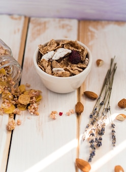 Bowl of cornflakes near spilled jar of granola and dry fruits on wooden surface