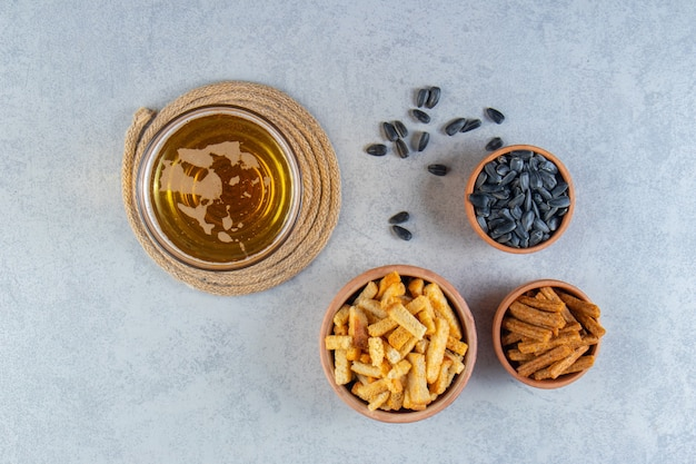 Bowl of croutons and seed next to beer in a glass , on the marble surface.
