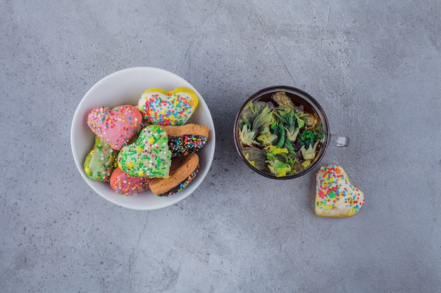 Bowl of delicious cookies with sprinkles and cup of tea on stone background.