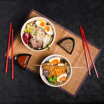Bowl of different noodles with salad; eggs; sauce and coriander seeds with chopsticks on placemat against black background