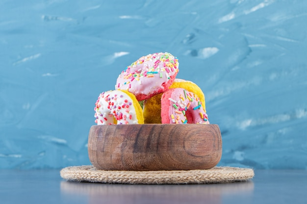 A bowl of donuts on a trivet on the marble surface