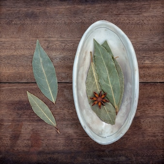 The bowl of dried bay leaves on old wooden background.