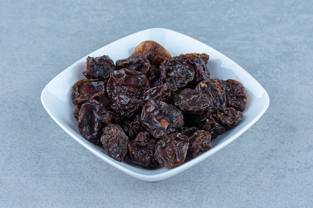 A bowl of dried cherry, on the marble table.