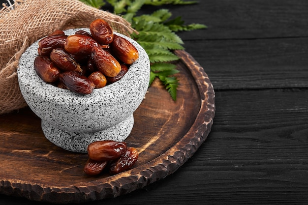 Bowl of dried dates on dark wooden background from side view
