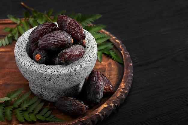 Bowl of dried dates on dark wooden space from side view