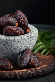 Bowl of dried dates on dark wooden table