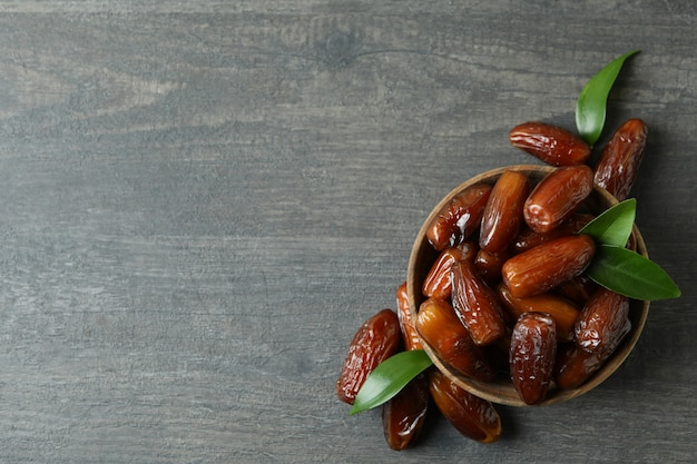 Bowl of dried dates on gray textured background