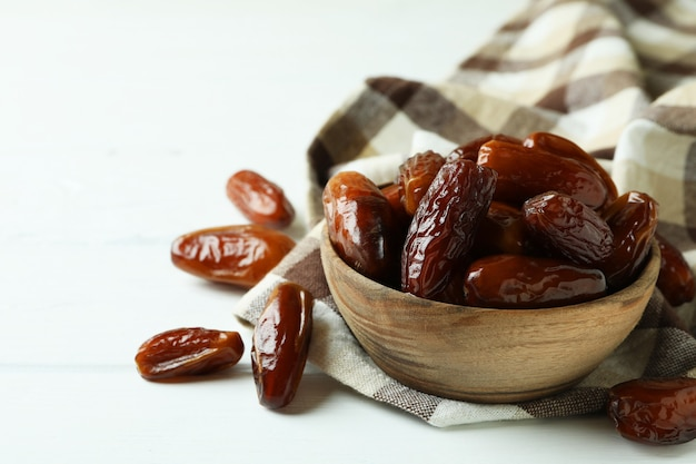 Bowl of dried dates on kitchen napkin on white wooden background