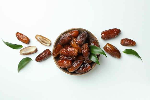 Bowl of dried dates with leaves on white