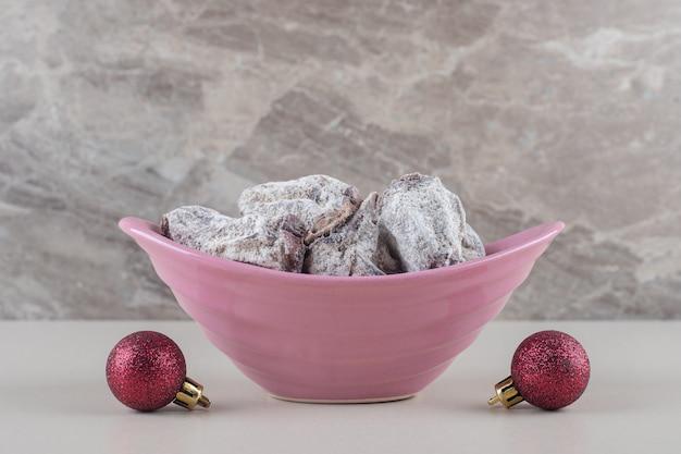 Ciotola di kaki essiccati ricoperti di zucchero in polvere accanto a baubles su sfondo marmo.
