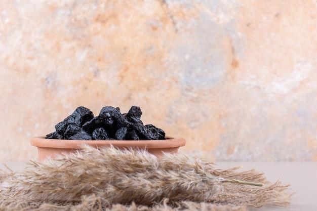 Ciotola di frutta secca di prugne posta su sfondo bianco. foto di alta qualità