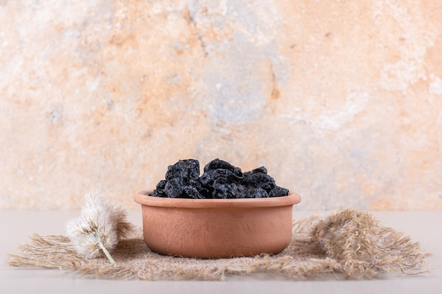 Bowl of dried plum fruits placed on white background. high quality photo