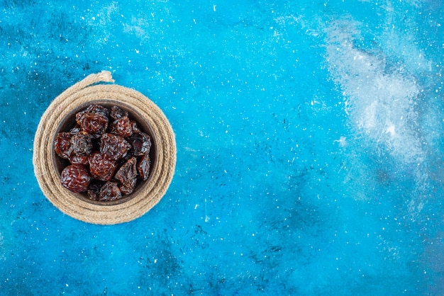 A bowl of dried plums on a trivet on the blue surface