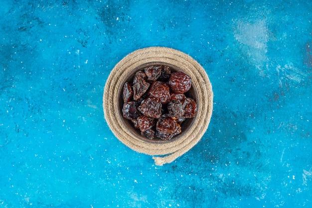 Una ciotola di prugne secche su un sottopentola, sul tavolo blu.