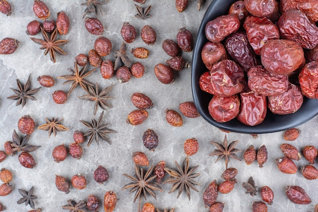 Bowl of dried rosehips on stone table.