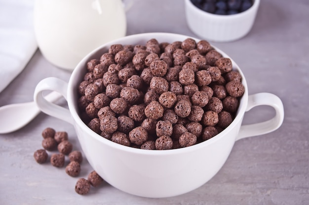 A bowl of dry chocolate balls cereal and bottle if milk on the gray table for health breakfast