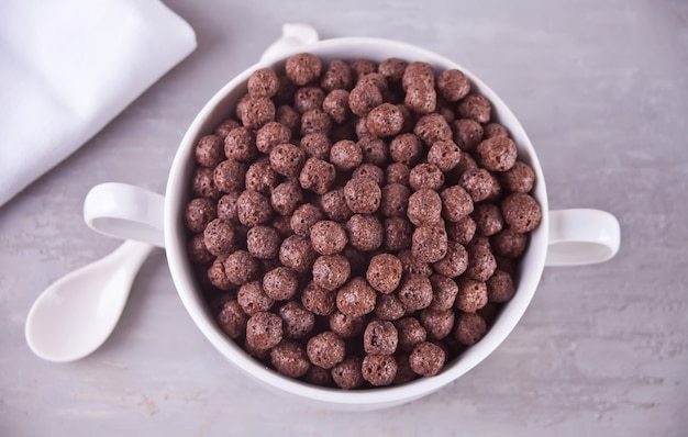 A bowl of dry chocolate balls cereal on the gray table for health breakfast