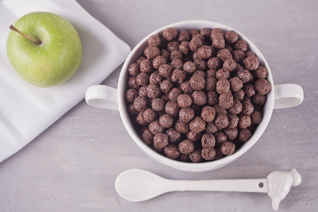 A bowl of dry chocolate balls cereal and green apple on the gray table for health breakfast