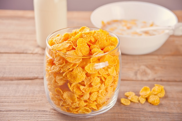 A bowl of dry corn flakes cereal on wood