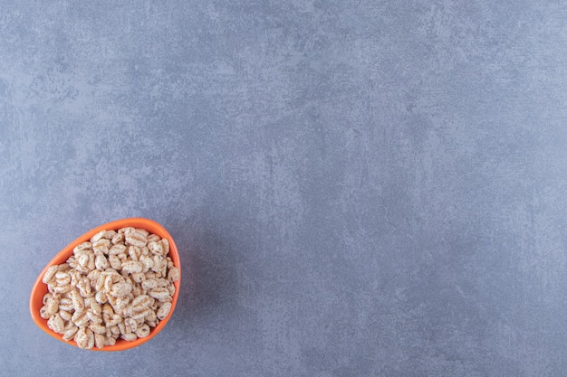 A bowl of dry cornflakes , on the blue background.