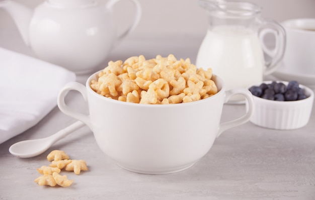 A bowl of dry star shaped cereal and a bottle of milk