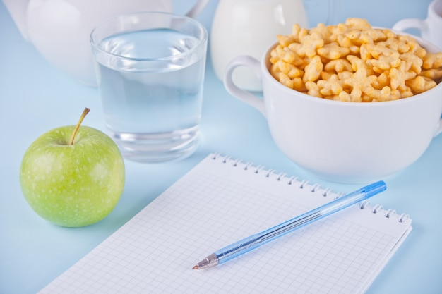 A bowl of dry star shaped cereal, cup of water, green apple