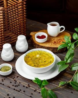 Una scodella di zuppa di gnocchi di dushbara servita con granelli di menta secca