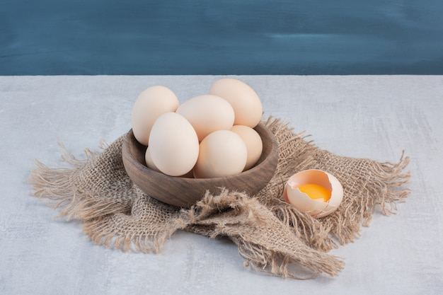 Bowl of eggs next to yolk in a shell on a piece of cloth on marble table.