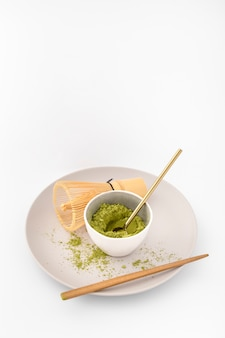 Bowl filled with matcha powder on a plate
