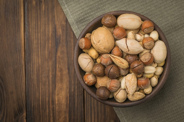 A bowl filled with a mixture of different nuts on a piece of cloth on a wooden table. vegetarian food.