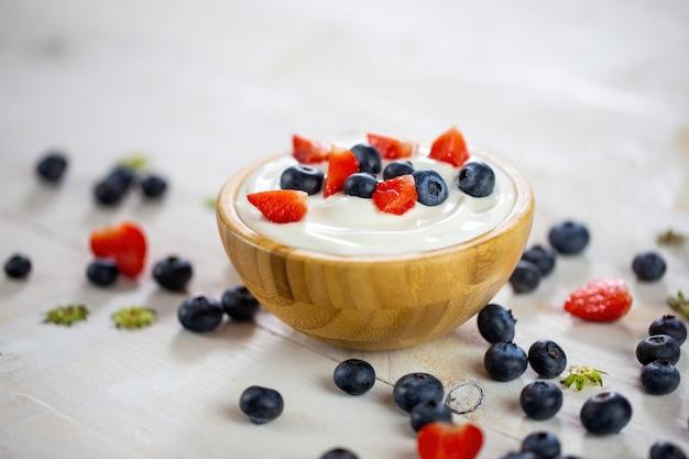 Чаша с йогуртом и ягодами на белом столе