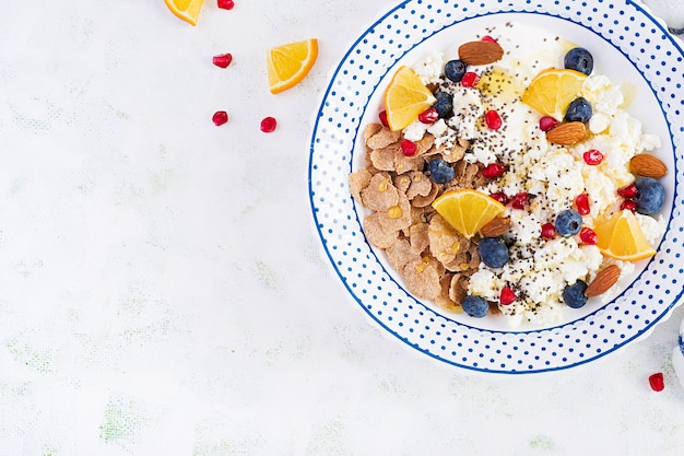 Bowl of flakes with cottage cheese and yogurt, blueberryes and pomegranate on white table