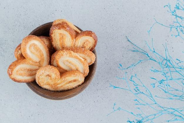 Ciotola di biscotti a fiocchi e rami decorativi su fondo di marmo.