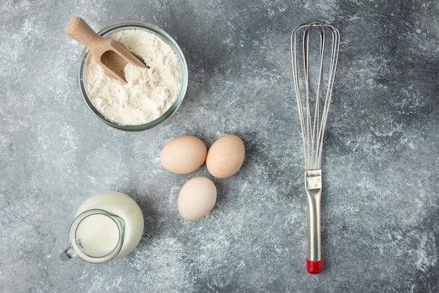 Ciotola di farina, uova e whisker sulla superficie di marmo.