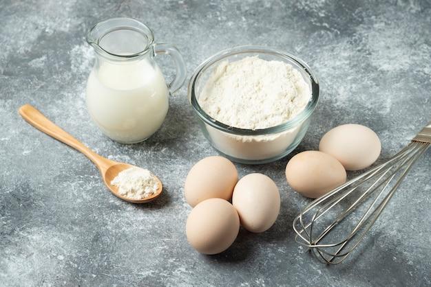 Ciotola di farina, uova e baffo su marmo.