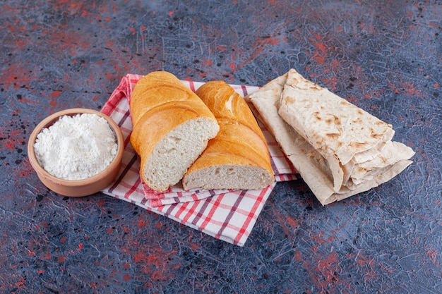 Una ciotola di farina, lavash e pane a fette su uno strofinaccio, sul blu.